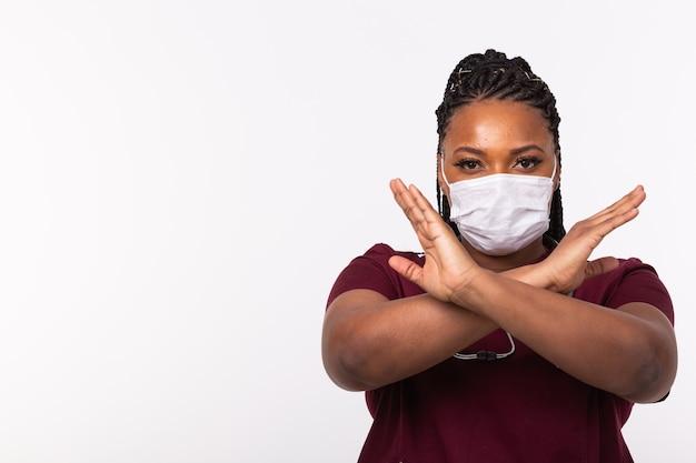 Medico incrociate le mani sul petto sul muro bianco con copia spazio. indossa una maschera medica. no o