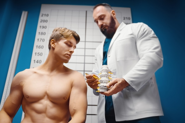 Il medico mostra i reparti dell'ernia delle vertebre della colonna vertebrale e le sue lesioni