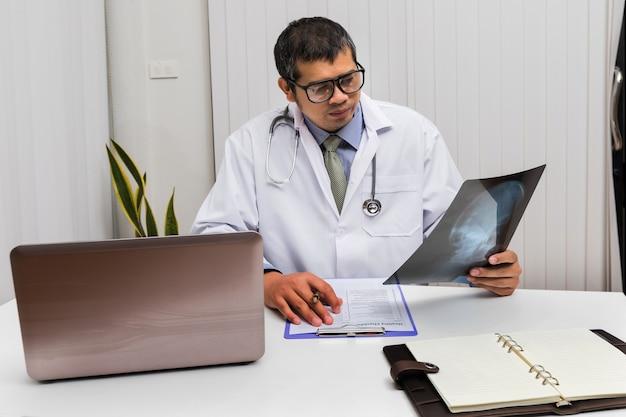 Medico diagnosticare e analizzare su pellicola a raggi x del paziente