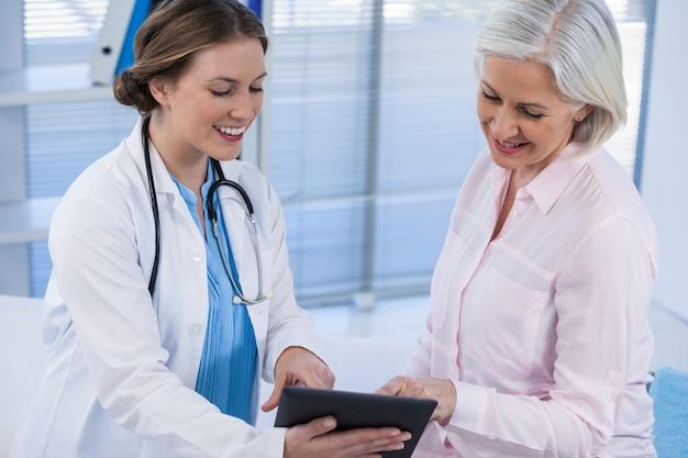 Medico che discute con il paziente sulla tavoletta digitale