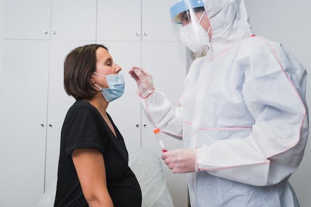 Un medico che esegue una pcr per rilevare il covid 19 su una donna incinta