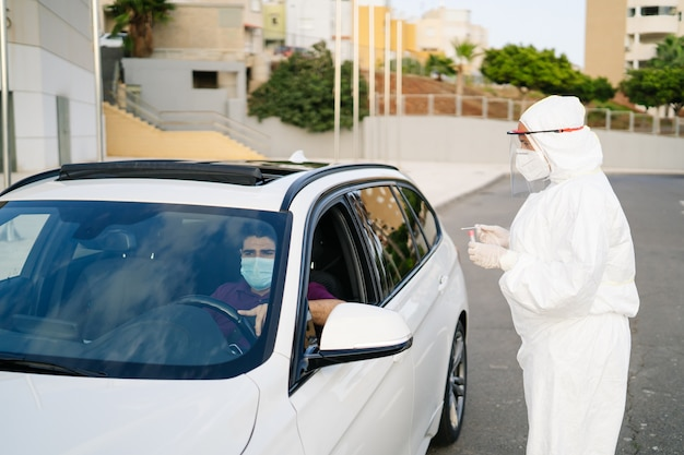 Medico che esegue un test pcr covid-19 su un paziente attraverso il finestrino dell'auto.