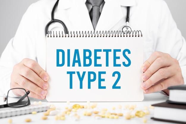 Il dottore in vestaglia tiene un blocco note con testo diabete di tipo 2, concetto medico