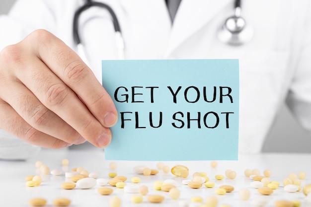 Il dottore in vestaglia tiene un adesivo con il testo get your flu shot