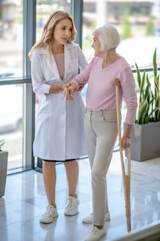Un dottore e una donna anziana con una stampella camminano in un corridoio e parlano
