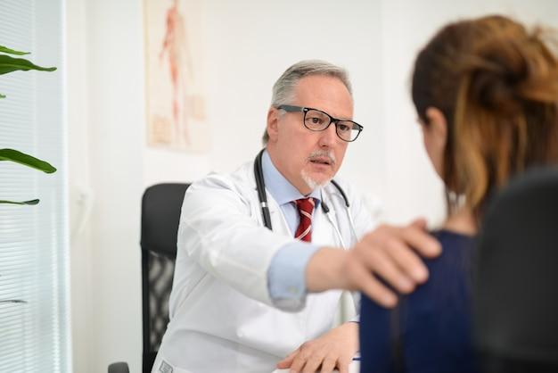 Medico che incoraggia un paziente malato nel suo studio