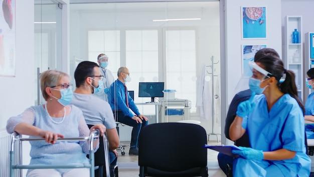 Medico in sala d'esame che ascolta i polmoni del paziente anziano con lo stetoscopio visiera del personale medico contro il coronavirus nella discussione con il womam senior disabile nell'area di attesa dell'ospedale.
