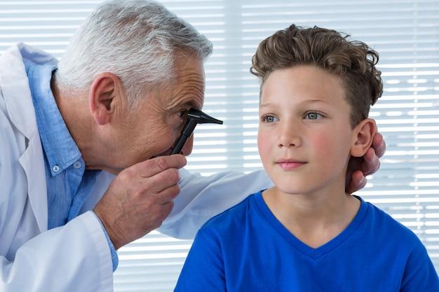 Il medico esamina l'orecchio del paziente