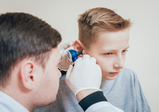 Il medico esamina l'orecchio del ragazzo con otoscopio. attrezzature mediche