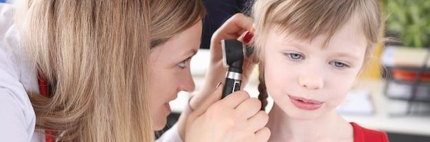 Il medico esamina l'orecchio con un otoscopio per il test dell'udito della bambina nel concetto di bambini