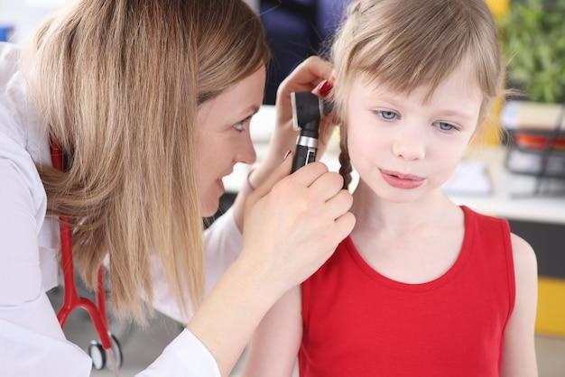 Il medico esamina l'orecchio con un otoscopio alla bambina