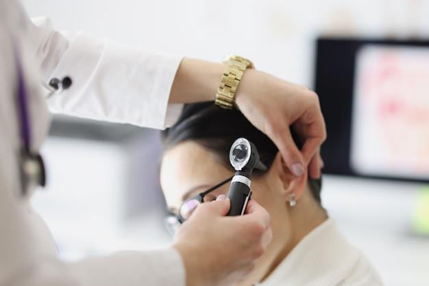 Il medico esamina l'orecchio del paziente con il primo piano dell'otoscopio