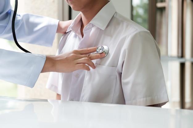 Il medico esamina un paziente con uno stetoscopio.