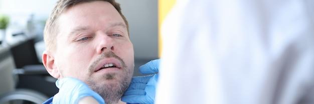 Il medico esamina la ghiandola tiroidea dei pazienti nel concetto di malattia della tiroide dell'ufficio medico