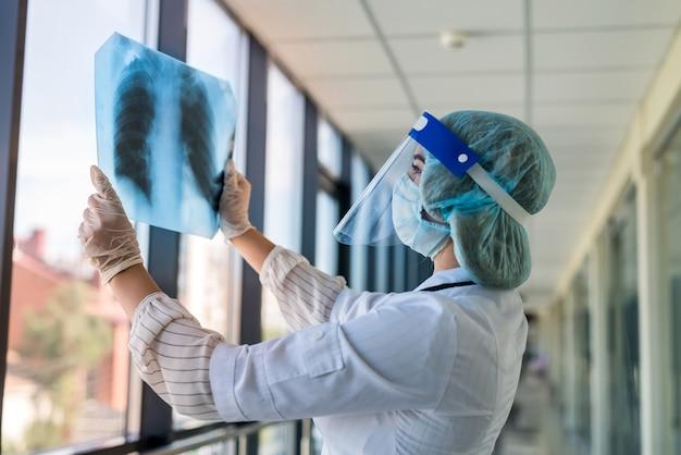 Il medico esamina l'immagine a raggi x dei polmoni nella visiera e nella maschera per determinare la polmonite causata da un nuovo virus covid19