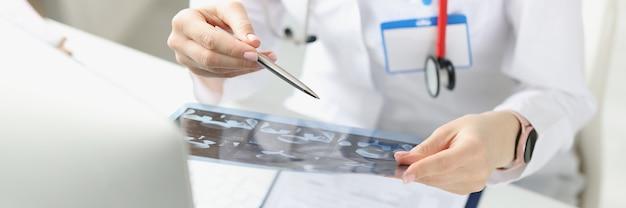 Il medico esamina i raggi x del paziente al tavolo di lavoro