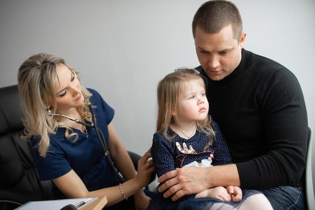 Medico che esamina una bambina dallo stetoscopio