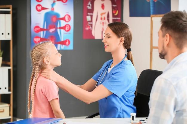 Medico che esamina bambina con problemi alla ghiandola tiroidea in clinica