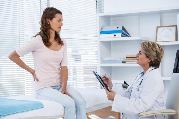 Medico che esamina la schiena di un paziente