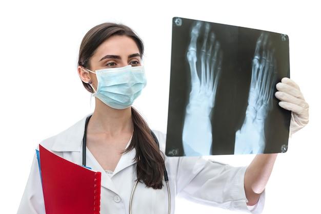Medico che esamina i raggi x del paziente isolato sulla parete bianca
