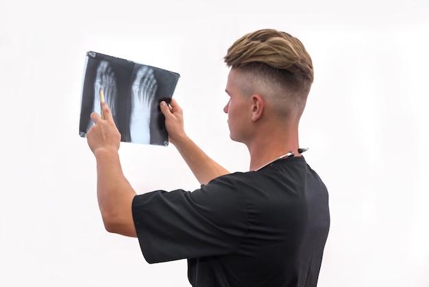 Medico che esamina i raggi x del paziente. giovane in uniforme blu che tiene i raggi x del piede e lo guarda