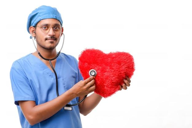 Medico che esamina un cuscino a forma di cuore rosso con uno stetoscopio su sfondo bianco.