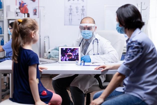 Medico che spiega il coronavirus a madre e figlio durante la consultazione