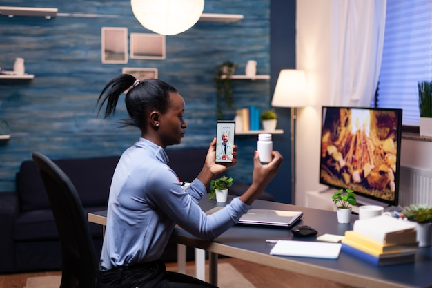 Medico che spiega il trattamento a una donna dalla pelle scura durante una videochiamata a tarda notte mentre tiene in mano una bottiglia di pillole. paziente nero in una videochiamata con un medico che discute problemi di salute della donna.