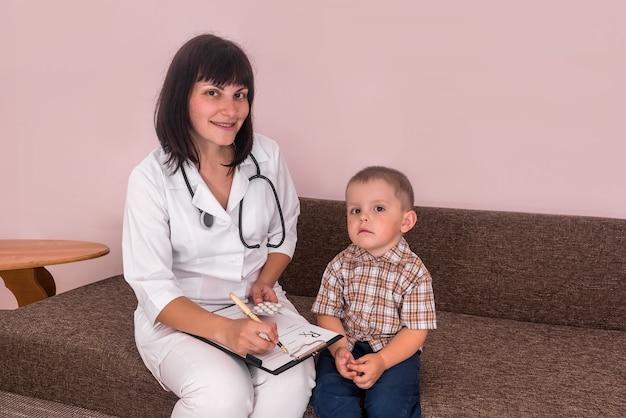 Medico che riempie la prescrizione e il ragazzino che si siede vicino