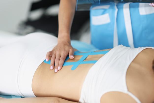 Il medico ripara il nastro kinesio sulla colonna vertebrale in un paziente con mal di schiena