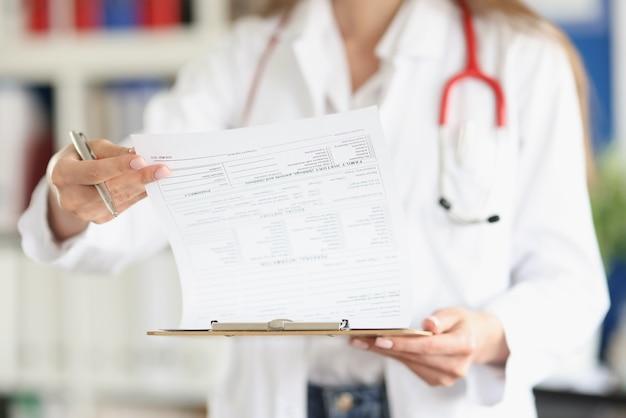 Medico che sfoglia i documenti nell'anamnesi del paziente in primo piano della clinica