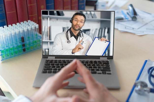 Dottore davanti al monitor di un laptop durante una conversazione in videochiamata online con un collega