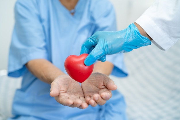 Il dottore dà un cuore rosso a una paziente asiatica anziana o anziana, un concetto medico sano e forte