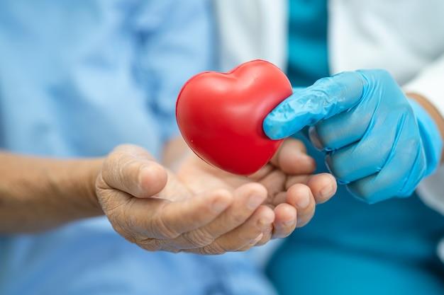 Il dottore dà un cuore rosso a una paziente asiatica anziana