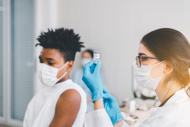 Il dottore dà un colpo al ragazzo africano e si fa vaccinare durante la pandemia di coronavirus o covid-19 in ospedale, concetto di vaccinazione