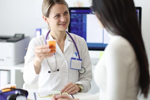 Medico che dà la bottiglia paziente di medicina in clinica.