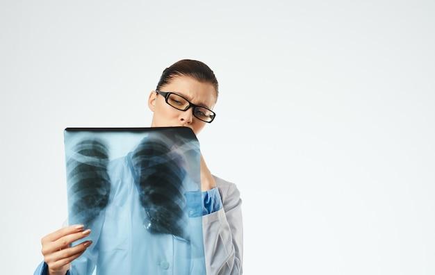 Dottore in occhiali e in un camice medico con una radiografia in mano. foto di alta qualità