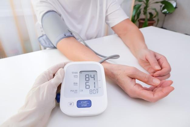 Il dottore in guanti misura la pressione sanguigna a una persona, sfondo bianco.
