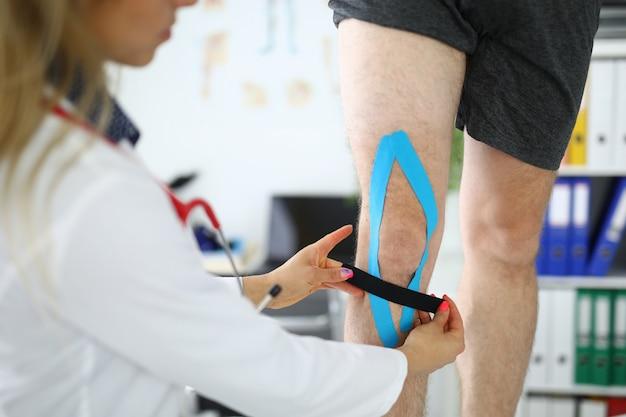 Il medico incolla un nastro elastico sulla gamba del paziente. protezione da lesioni e distorsioni