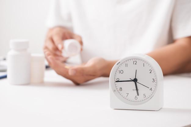 Mano del medico che tiene la pillola della medicina di erbe con l'orologio e la bottiglia, concetto medico di tempo