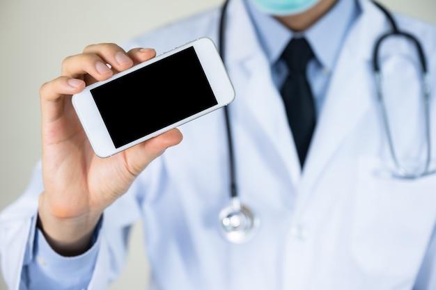Mano di medico che tiene smartphone