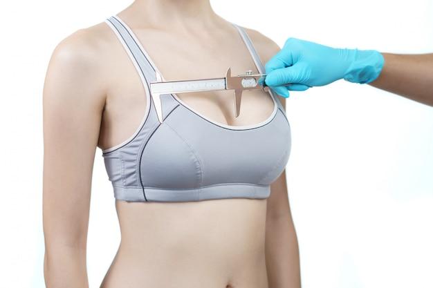 Seno di donna misura medico mano con pinza. concetto di chirurgia della protesi mammaria.