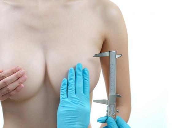 Seno di donna misura medico mano con pinza