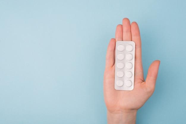 Mano di medico che allunga la mano al paziente e dà il concetto di pillole. in alto sopra la prima persona sopraelevata pov vista ravvicinata foto di una mano di giovane femmina azienda blister con pillole sfondo isolato