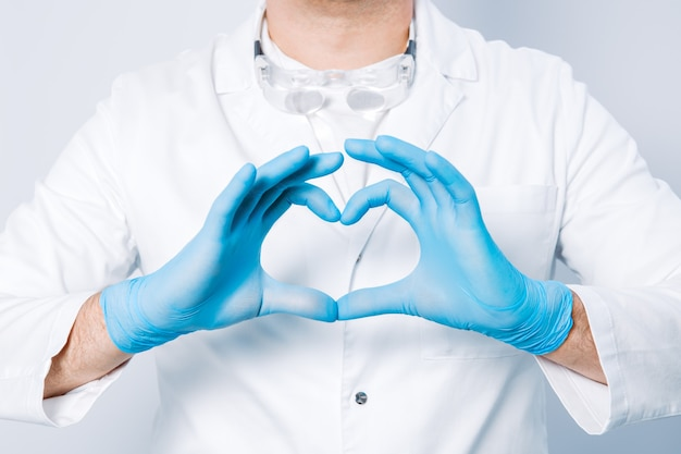 Mani del medico in guanti a forma di cuore contro la superficie del suo corpo e camice medico