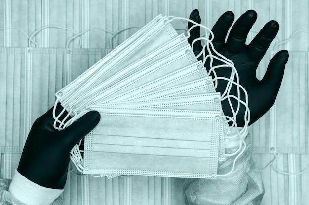 Mani del medico che tengono molte maschere chirurgiche mediche in guanti protettivi. colorazione dell'immagine concettuale nella tendenza tidewater green color dell'anno 2021 sullo sfondo delle bende respiratorie per il viso umano.