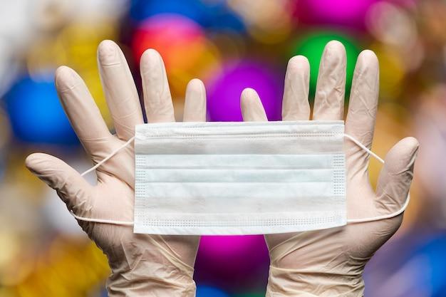 Mani del medico che tengono la maschera medica in guanti bianchi su sfondo bokeh decorazioni di palle di happy new years. concetto di quarantena per le feste natalizie a causa della malattia covid-19 della crisi del coronavirus
