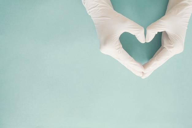 Mani del medico con guanti a forma di cuore, donazione, concetto di giornata mondiale del cuore