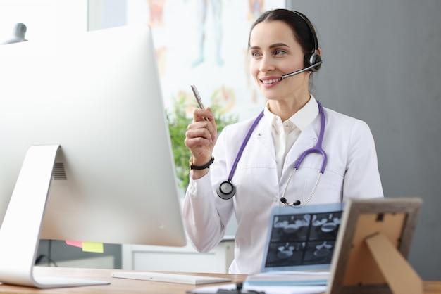 Medico in cuffia che comunica con il paziente tramite collegamento video. concetto di consulti medici online
