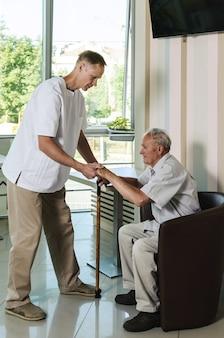 Il dottore aiuta un vecchio ad alzarsi dalla sedia